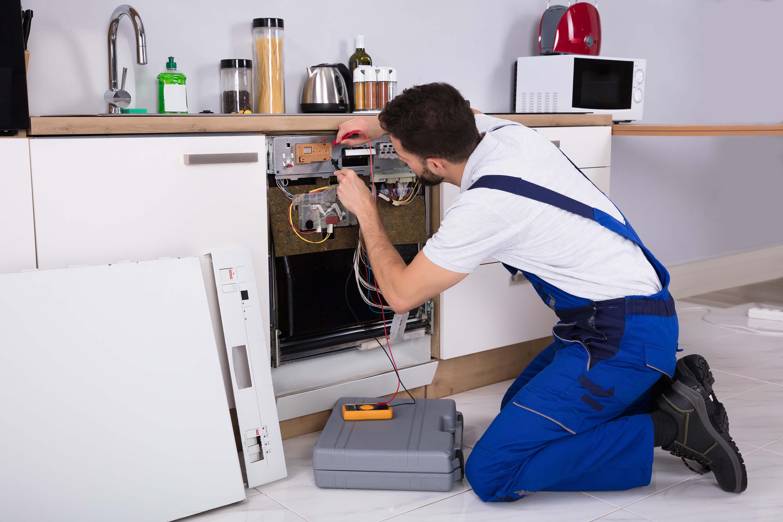 workman fixing a dishwasher